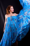 Girl in blue dress dancing Stock Images