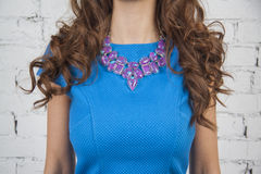 Girl in blue  dress demonstrates mauve necklace Royalty Free Stock Photos