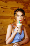 Girl in a blue dress drinking cappuccino Royalty Free Stock Image