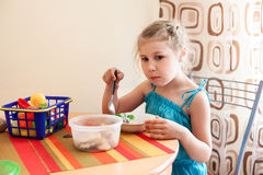 Girl in blue dress eating porridge at table and plays with her toys Royalty Free Stock Photo