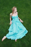Girl in the blue dress on the green grass Royalty Free Stock Photography