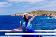 Girl in blue dress and hat have a voyage on a boat. Happy redhead girl in blue dress and hat have a voyage on a boat in Greece. Summertime vacation concept Stock Photo