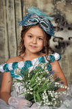 Girl in blue dress hold snowdrops Stock Images