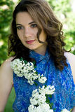 The girl in a blue dress holding a branch with flowers Stock Photo
