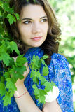 The girl in a blue dress holding a branch with flowers Royalty Free Stock Photo