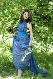 The girl in a blue dress holding a branch with flowers Royalty Free Stock Photos