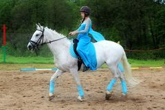The girl in the blue dress on horseback. Royalty Free Stock Images