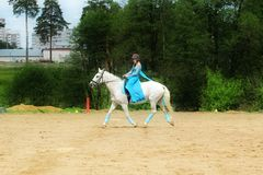 The girl in the blue dress on horseback. Royalty Free Stock Photography