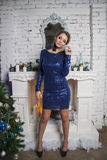 Girl in blue dress near christmas decorated commode Royalty Free Stock Photos