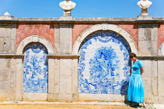 Girl in blue dress near wall with blue azulejo Stock Images