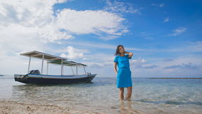 The girl in the blue dress on the ocean. Against the backdrop of turquoise clean ocean yacht and clear skies. Bali is stock video footage