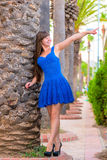 Girl in a blue dress is pointing in the direction Stock Photos