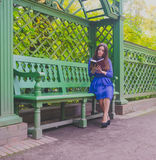 Girl in blue dress reading a book sitting on the bench Royalty Free Stock Photos