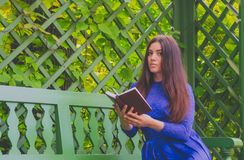 Girl in blue dress reading a book sitting on a bench outside the green fence closeup Stock Photos
