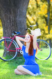 Girl in blue dress with red bicycle Stock Photography