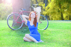 Girl in blue dress with red bicycle Stock Images