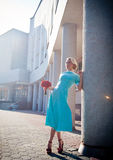 The girl in a blue dress with red flowers in a Royalty Free Stock Photography