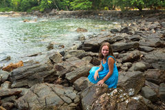 Girl in a blue dress in the rocks of the sea coast. Royalty Free Stock Photography
