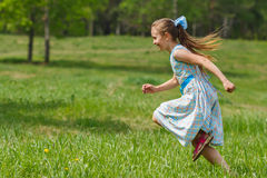 Girl in blue dress running at city park. Child girl in blue dress running at green meadow stock photography