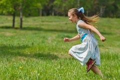 Girl in blue dress running at city park. Child girl in blue dress running at green meadow Stock Photography