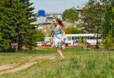 Girl in blue dress running at city park. Girl laughing and running at city park Stock Image