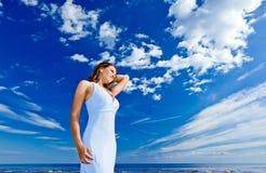 Girl in blue dress on seacoast Stock Photo