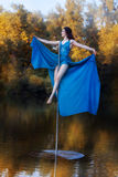 Girl in a blue dress sits high on pole dance. Royalty Free Stock Images