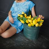 A girl in a blue dress sits next to a metal basin with yellow tulips stock images