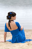 Girl in a blue dress sitting Royalty Free Stock Images