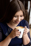 The girl in the blue dress sitting with a cup of cappuccino. Coffee smiling face Stock Image