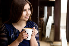 The girl in the blue dress sitting with a cup of cappuccino. And looking out the window Royalty Free Stock Image