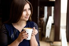 The girl in the blue dress sitting with a cup of cappuccino and looking out the window. The girl in the blue dress sitting with a cup of cappuccino smiling Royalty Free Stock Photos