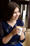 The girl in the blue dress sitting with a cup of cappuccino smiling looking. Through a window Stock Photography