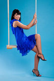 Girl in the blue dress sitting on swings Stock Images