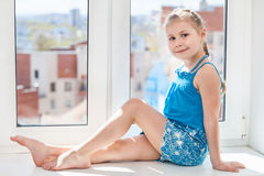Girl in blue dress sitting on windowsill in sun light Stock Image