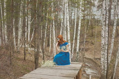 Girl in blue dress in the spring forest stay on a  Royalty Free Stock Image