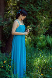 Girl in blue dress standing near a tree. Royalty Free Stock Image