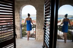 Girl in the blue dress stands in the doorway. With blinds Royalty Free Stock Image