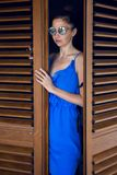 Girl in the blue dress stands in the doorway. With blinds Stock Images