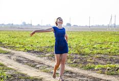 Girl in a blue dress strolls in the field of melons. Joyful emotions when walking in nature. Girl in a blue dress strolls in the field of melons. Joyful Stock Image