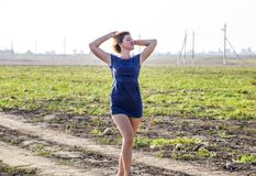 Girl in a blue dress strolls in the field of melons. Joyful emotions when walking in nature. Girl in a blue dress strolls in the field of melons. Joyful Stock Photography