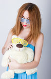 Girl in a blue dress and sunglasses in the style of disco, hugging a teddy bear in the same glasses.  royalty free stock image