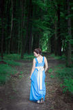 Girl in a blue dress walking on the green forest turns around Royalty Free Stock Photos