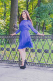 Girl in blue dress walking in the Park approached the railing of the bridge Royalty Free Stock Image
