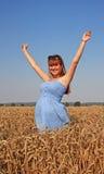 Girl in blue dress walking on wheat field Stock Image