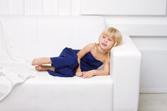 Girl is in blue dress on a white sofa Royalty Free Stock Images