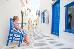 Girl in blue dresses having fun outdoors on Mykonos streets. Cute girl in blue dress at street of typical greek traditional village with white walls and colorful Stock Photo