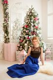A girl in a blue evening dress next to a Christmas tree. New Year`s Eve. Christmas. A girl in a blue evening dress sitting next to a Christmas tree Stock Images