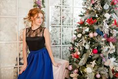 A girl in a blue evening dress next to a Christmas tree. New Year`s Eve. Christmas. A girl in a blue evening dress sitting next to a Christmas tree Stock Image
