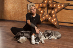 Girl with blue eyed beautiful husky puppies Stock Image